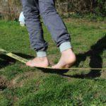 Kinderfüsse balancieren auf Slag-Line
